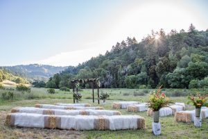 an idyllic country wedding with linen draped hay bales in a field at Bell Valley Retreat in Boonville, Anderson Valley, California