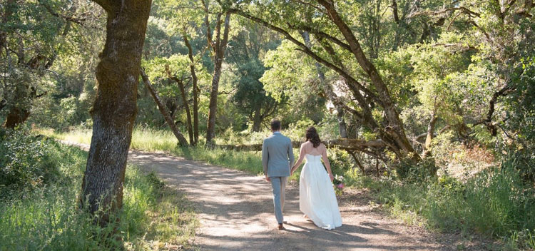 a couple walk down the wooded road at The Toll House at Bell Valley Retreat in Anderson Valley, Mendocino County, California
