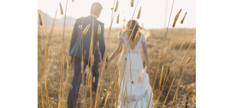 couple walks through a meadow during their wedding at The Toll House at Bell Valley Retreat in Anderson Valley, Mendocino County, California