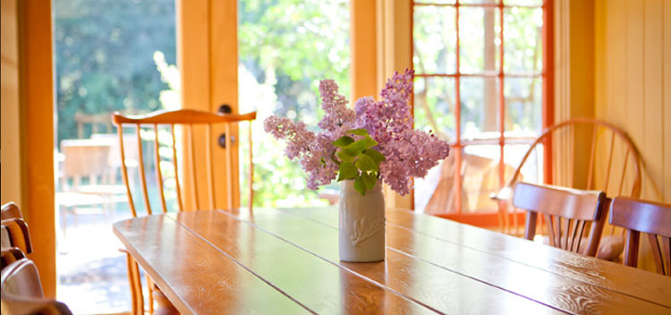 a jar of lilacs on the dining room table at the Toll House at Bell Valley Retreat