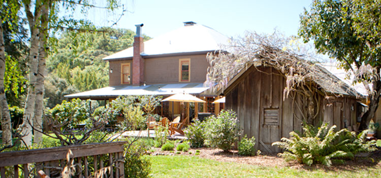 an outside view of the Toll House on a sunny day at Bell Valley Retreat