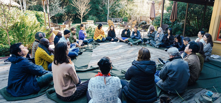 a circle of retreat participants meditating on the deck