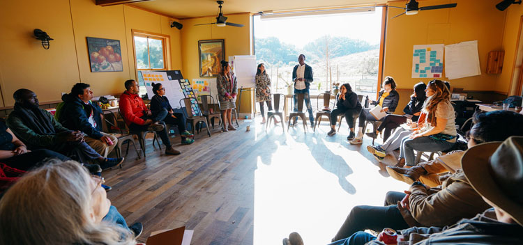 a group of retreat participants circle up to have a conversation on the ground floor of the Barn with sunlight pouring in through open doors