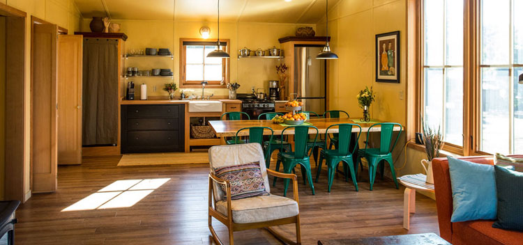 barn living space upstairs with dining table and open plan kitchen
